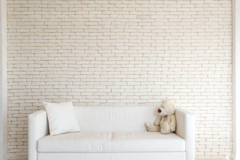 Contentbär sitzt auf weißer Couch